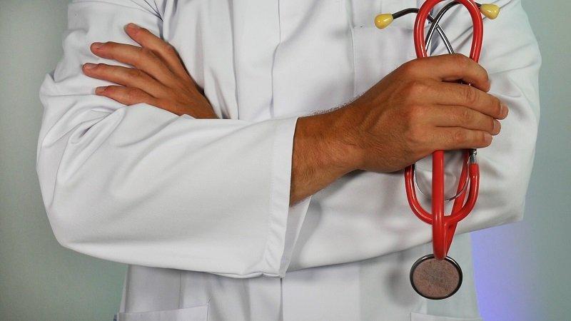 Arzt im Kittel hält Stethoskop
