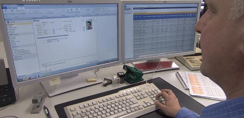 Mann sitzt vor einem Computer-Bildschirm mit der Flüchtlingsakte von enaio®