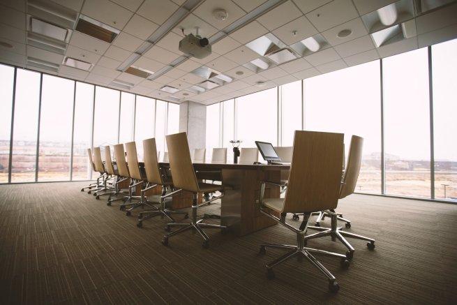 Sitzungsraum mit Stühlen und Tisch vor einer Fensterfront