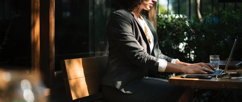 Eine Frau arbeitet an einem Tisch im Freien an einem Laptop