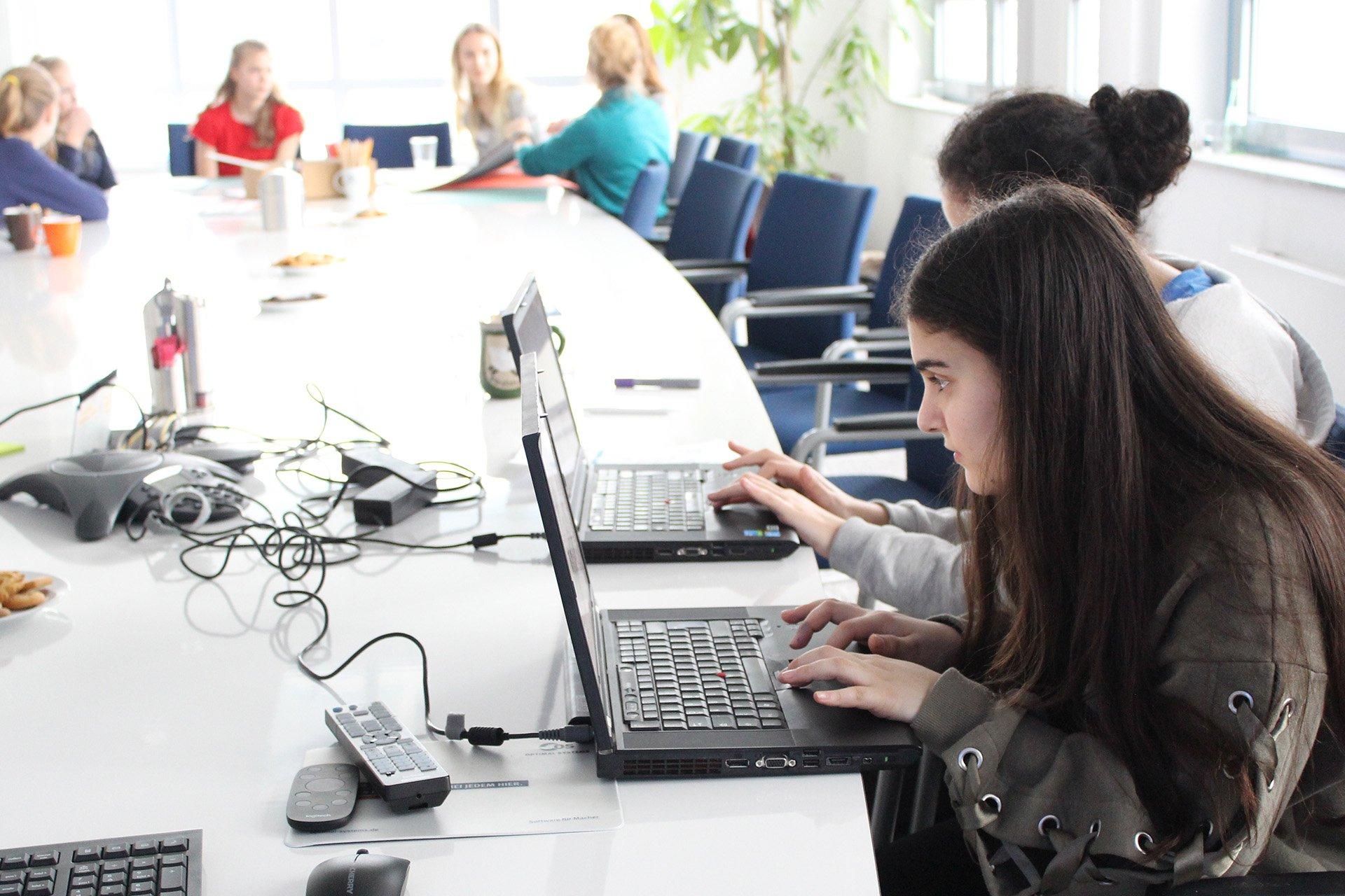 Mädchen arbeiten konzentriert an Laptops