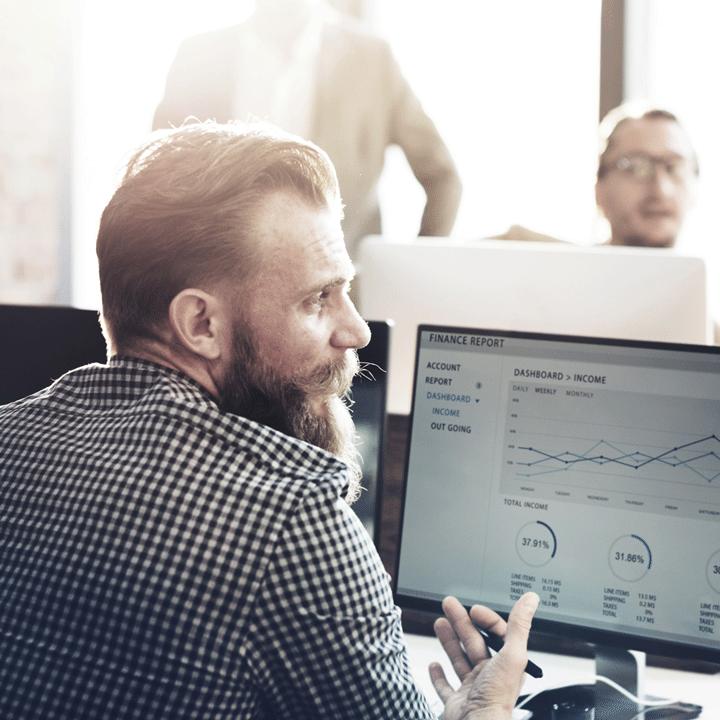Mann mit Bart sitzt gestikulierend vor einem Monitor