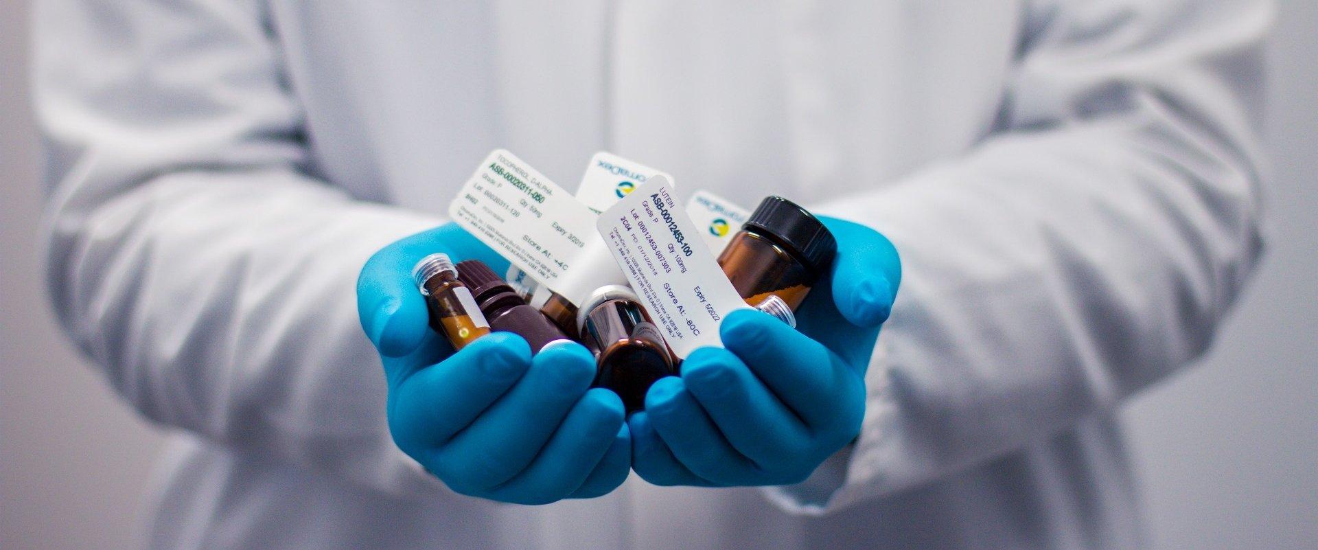 Nahaufnahme Hände in Handschuhen mit Arzneimitteln