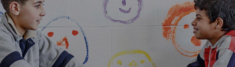 Zwei Jungs, die sich vor einer Wand mit gemalten Gesichtern unterhalten