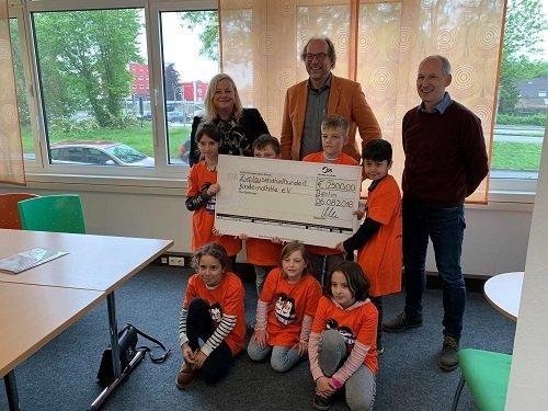 Gruppenfoto einer Spendenübergabe von OPTIMAL SYSTEMS Dortmund an die Kindernothilfe