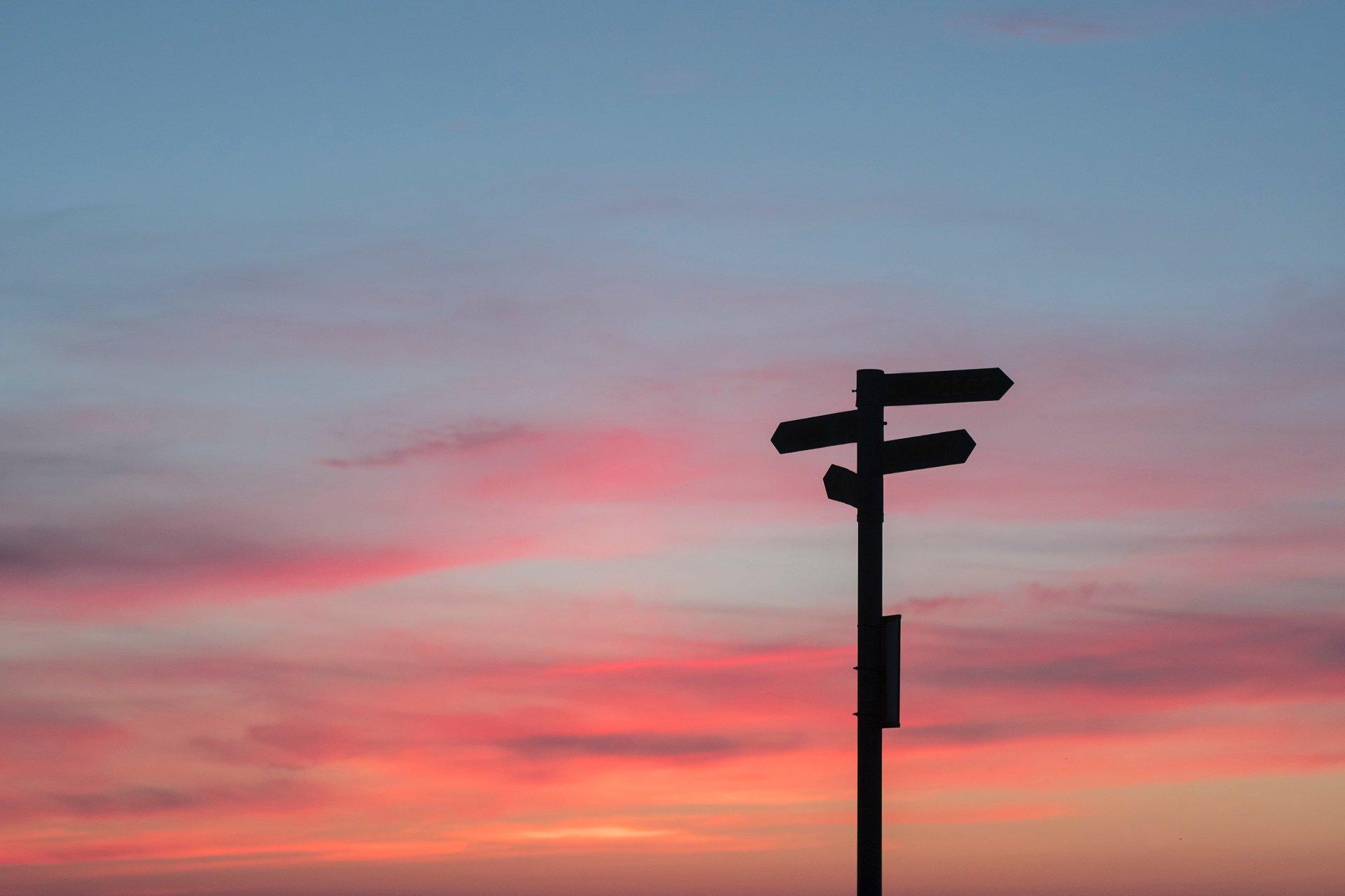 Ein Schild mit Wegweisern im Sonnenuntergang.