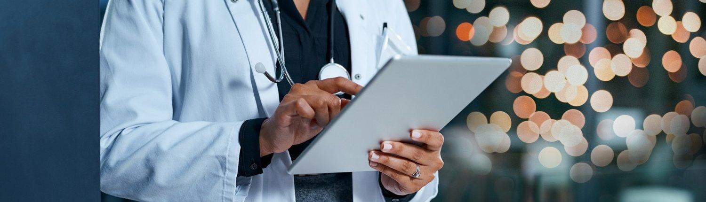 Nahaufnahme von Ärztin mit Stethoskop, die auf Tablet tippt.