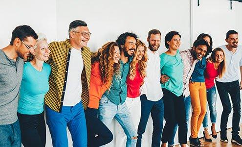 Einer Reihe fröhlicher Arbeitskollegen vor einer Wand stehend