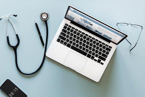 Laptop, Stethoskop, Handy und Brille auf einem Tisch