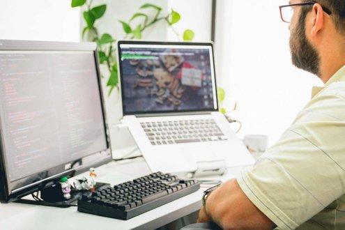 Mann am Arbeitsplatz mit Laptop, Monitor und Tastatur