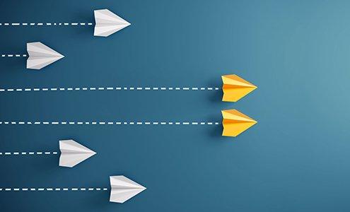Zwei gelbe Papierflieger auf blauem Hintergrund verfolgt von drei weißen Papierfliegern