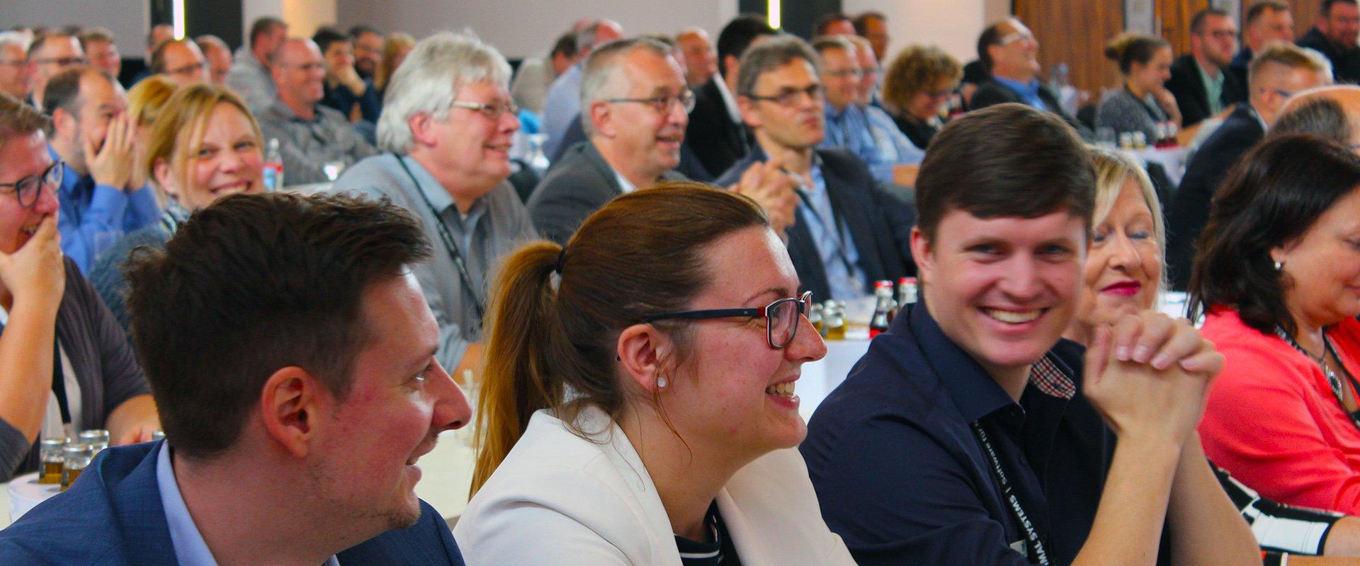 Lachende Teilnehmer einer Veranstaltung von OPTIMAL SYSTEMS