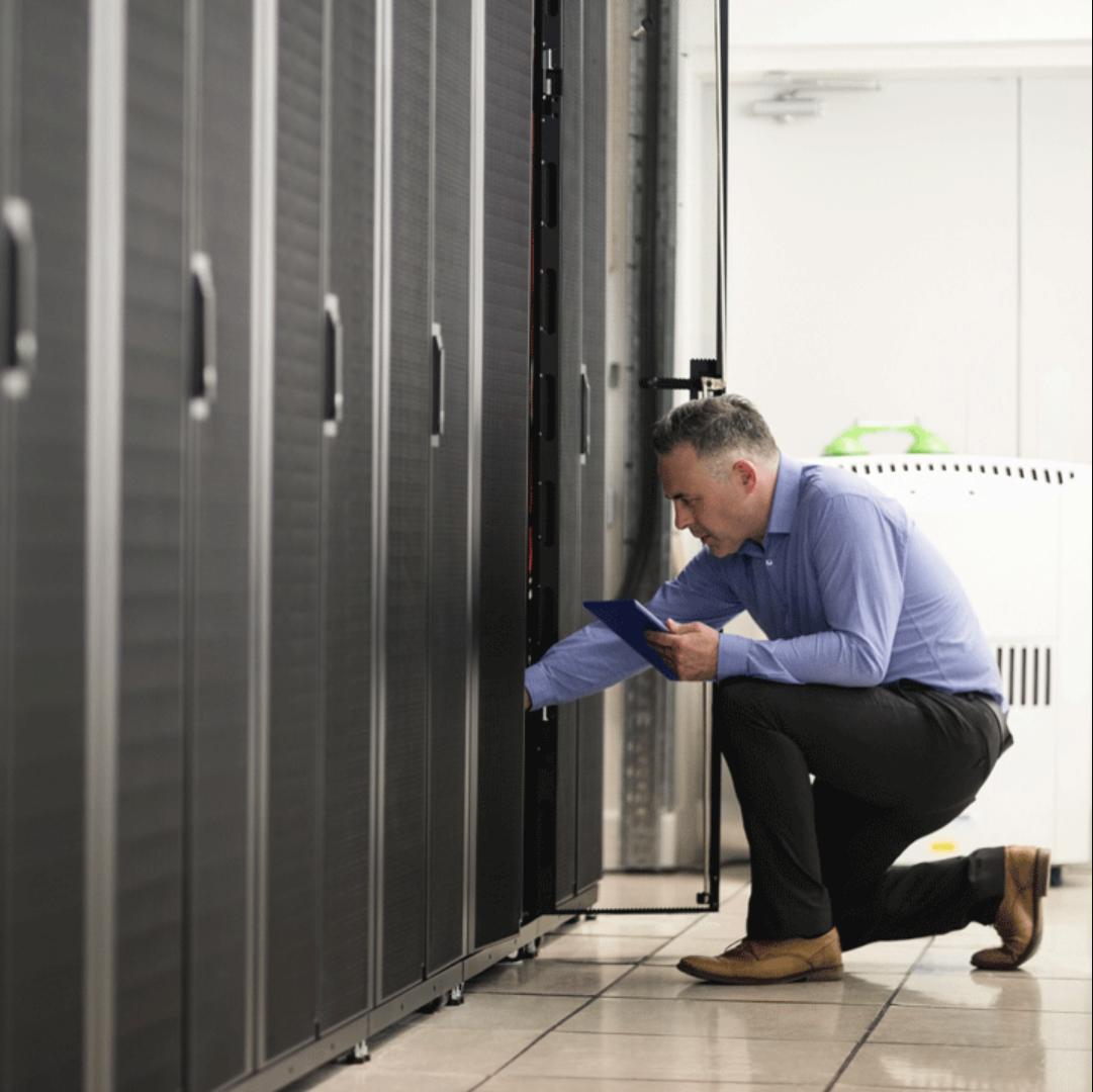 Mann arbeitet knieend an einem Server