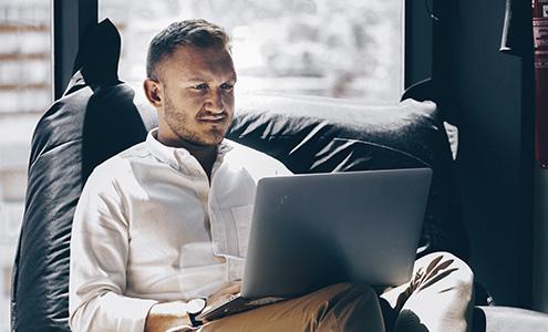 Mann sitzt lässig im Sitzkissen am Laptop