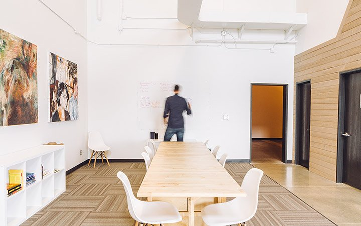 Mitarbeiter steht allein in einem hellen Konferenzraum