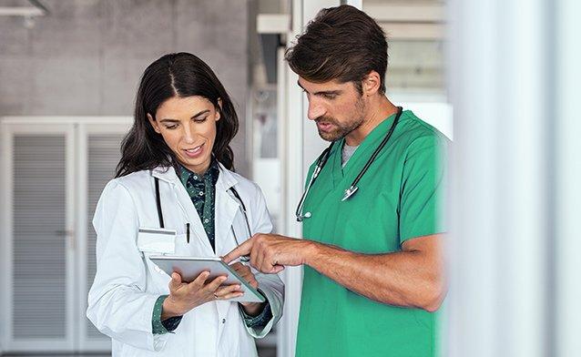 Ärztin und Arzt kucken gemeinsam auf ein IPad Rechnungseingang