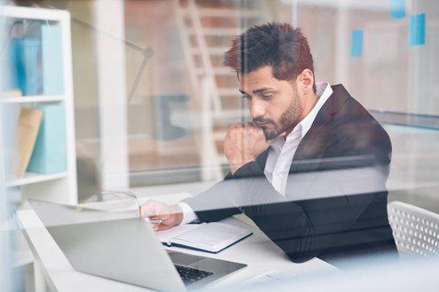 Ein Mann im Anzug schaut nachdenklich auf ein Laptop