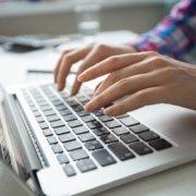 Person schreibt an einem Laptop