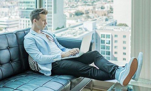 Mann sitzt auf der Couch vor dem Fenster am Rechner