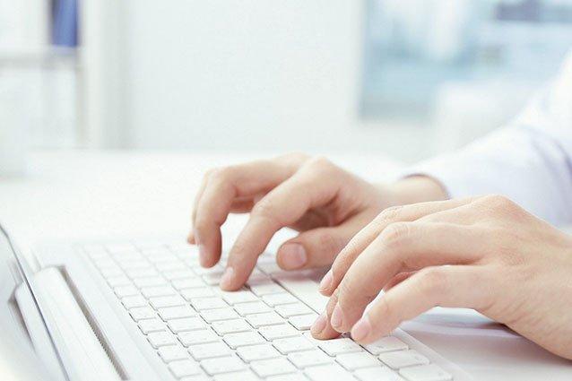 Hände auf Laptop-Tastatur