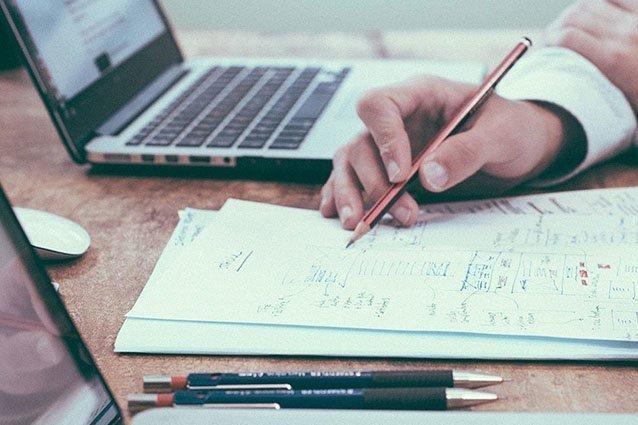 Laptop mit Unterlagen auf Tisch