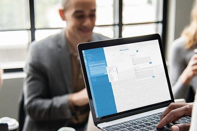 Mann tippt auf Laptop mit Menschen im Hintergrund
