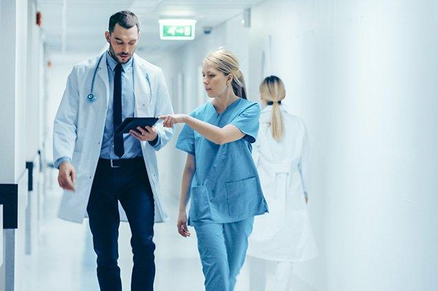 Arzt und Ärztin mit Ipad auf dem Gang
