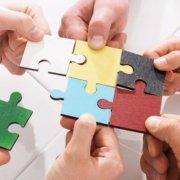 Hände setzen ein Puzzle zusammen