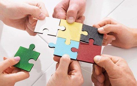 Hände halten Puzzle Teile fest