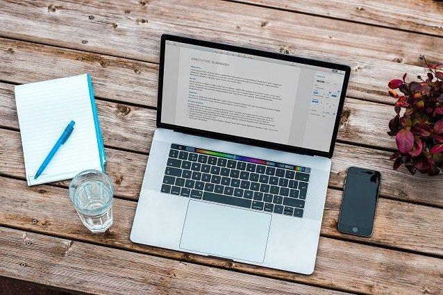 Laptop und Notizblock auf Tisch Beitragsbild