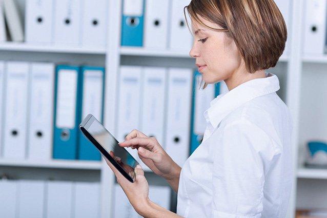 Frau in der Verwaltung am Tablet