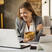 Frau beim Frühstück vor dem Computer