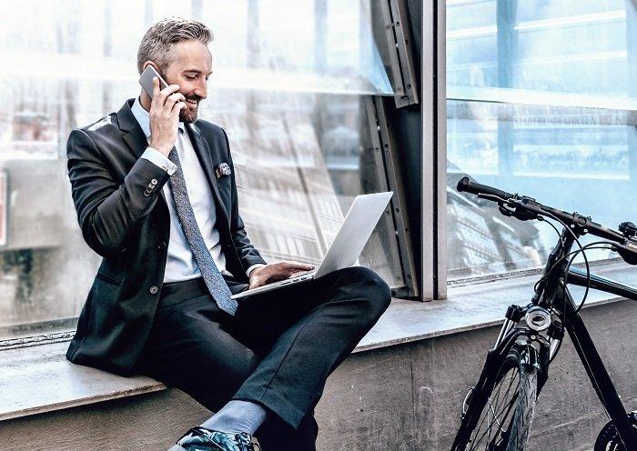 Mann lässig mit Laptop auf der Fensterbank