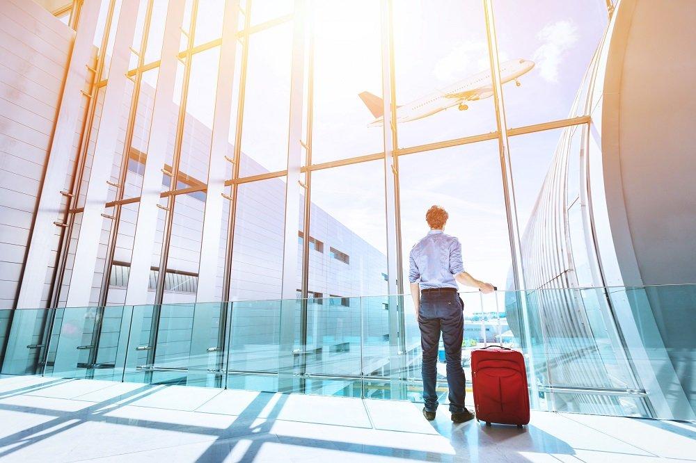 Mann mit Rollkoffer am Flughafen