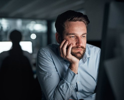 Mann sitzt gelangweilt vor dem Monitor